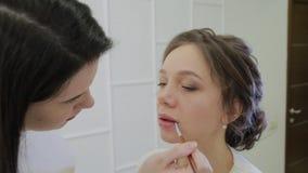 Визажист используя щетку для губной помады применения на женщине губ красивой Конец вверх по лоску губы применения на губах сток-видео