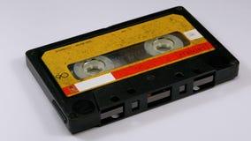 Винтажная желтая магнитофонная кассета вращает на белой предпосылке видеоматериал
