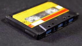 Винтажная желтая магнитофонная кассета вращает на черной предпосылке акции видеоматериалы