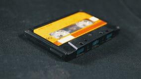 Винтажная желтая магнитофонная кассета вращает на черной предпосылке сток-видео