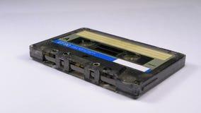 Винтажная магнитофонная кассета вращает на белой предпосылке видеоматериал
