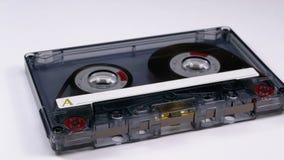 Винтажная прозрачная магнитофонная кассета вращает на белой предпосылке акции видеоматериалы