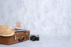 Винтажная сумка перемещения с аксессуарами лета морскими: ретро камера, парусник игрушки, шляпа пляжа Перемещение или туризм, лет стоковая фотография rf