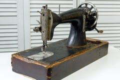 Винтажная швейная машина стоит на белой таблице стоковые фотографии rf
