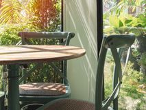 Винтажный деревянный стол и стул в стеклянной комнате около сада стоковое изображение
