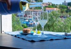 Вино кельнера лить белое на внешней террасе кафа стоковая фотография