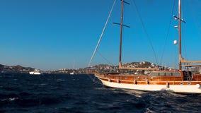 Вид на море и деревянный парусник в летнем времени в среднеземноморском, голубом небе, горах и чистом открытом море с ровными вол видеоматериал