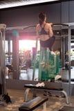 Вид сзади молодой привлекательной женщины вытягивая вверх на Chin вверх по тренировке бара в спортзале стоковые фото