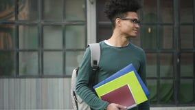 Вид спереди стоя счастливого и умного молодого ребенк студента школы с темными волосами держа его проект домашней работы и усмеха видеоматериал