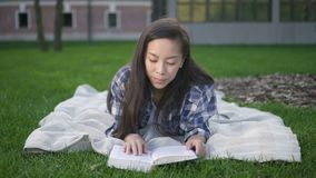 Вид спереди счастливой азиатской модели девушки студента с темными волосами делая исследование в зоне связи работая на проекте видеоматериал
