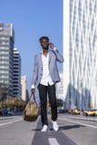 Вид спереди человека черного африканца молодого идя на улицу нося элегантную куртку и держа сумку пока используя телефон в солнеч стоковое фото rf