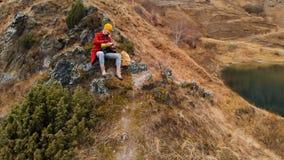 Вид с воздуха девушки сидя на утесе мыса на береге озера льет чай от thermos видеоматериал