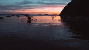 Вид с воздуха шлюпок и яхт в тропическом заливе на заходе солнца El Nido, Palawan, Филиппины Морской тропический заход солнца видеоматериал