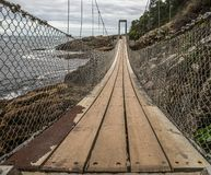 Висячий мост с деревянными floorboards и веревочками веревочки стоковое изображение
