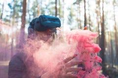 Виртуальная реальность женщины нося изумленные взгляды в лесе видит бомбы дыма Стекла VR стоковые фото