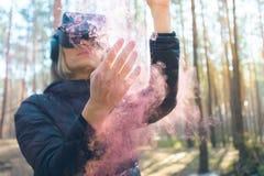 Виртуальная реальность женщины нося изумленные взгляды в лесе видит бомбы дыма Стекла VR стоковое изображение rf