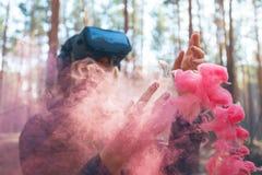 Виртуальная реальность женщины нося изумленные взгляды в лесе видит бомбы дыма Стекла VR стоковые изображения rf