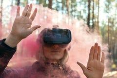 Виртуальная реальность женщины нося изумленные взгляды в лесе видит бомбы дыма Стекла VR стоковые изображения