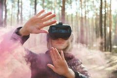 Виртуальная реальность женщины нося изумленные взгляды в лесе видит бомбы дыма Стекла VR стоковое фото
