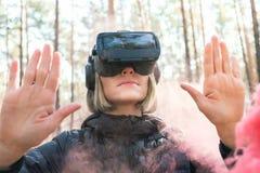 Виртуальная реальность женщины нося изумленные взгляды в лесе видит бомбы дыма Стекла VR стоковое фото rf
