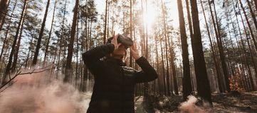 Виртуальная реальность женщины нося изумленные взгляды в лесе видит бомбы дыма Стекла VR стоковое изображение