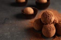 Вкусные трюфеля шоколада напудренные с какао на серой предпосылке стоковое изображение