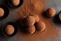 Вкусные трюфеля шоколада напудренные с какао на серой предпосылке стоковые изображения