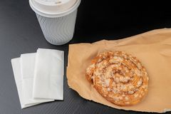Вкусный торт с сахаром на сером бумажном мешке Бумажный стаканчик кофе и сладкой закуски стоковые изображения rf