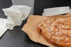 Вкусный торт с сахаром на сером бумажном мешке Бумажный стаканчик кофе и сладкой закуски стоковые фото