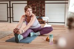 Внимательная женщина сидя на ее старой циновке йоги и нагревая стоковая фотография rf