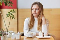 Внимательная красивая женщина сфокусировала задумчиво в сторону, выпивает эспрессо и ест очень вкусный торт в кофейне, наслаждает стоковые фотографии rf