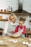 Внимательная коротк-с волосами белокурая дама направляя ее дочь стоковые фото