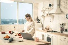Внимательная молодая женщина варя на аккуратной кухне стоковое изображение