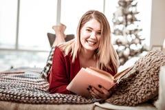 Внимательная молодая дама с темными ногтями нося книгу в твердом переплете стоковые фотографии rf