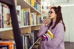 Внимательная положительная дама выбирая между 2 книгами стоковые изображения rf