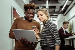 Внимательная дама с 2 оплетками делая фото из экрана с ее смартфоном стоковое изображение rf