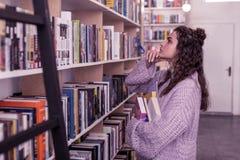 Внимательная длинн-с волосами женщина в сверхразмерном свитере касаясь ее подбородку стоковое фото