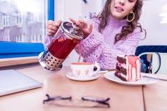 Внимательная осторожная дама лить горячий чай в милой чашке стоковое фото rf