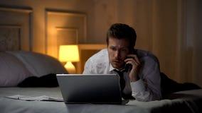 Внимательный мужской печатать на ноутбуке и говорить по телефону подготавливая отчет, крайний срок стоковая фотография
