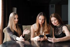 Всегда соединенный, наркомания интернета, маленькие девочки в кафе смотря их смартфоны, социальную концепцию сети стоковая фотография rf
