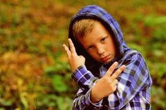 Вскользь холодно мальчик холодный Малый мальчик в вскользь hoodie Жест малой выставки ребенка оскорбляя Im немного из плохого мал стоковое фото rf