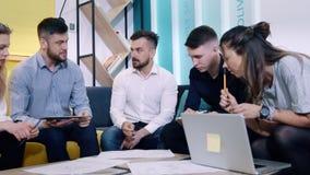 Встреча работников офиса Коллеги обсуждают план сидя на софе таблицей сток-видео