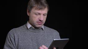 Всход крупного плана взрослого кавказского человека используя планшет перед камерой с предпосылкой изолированной на черноте видеоматериал
