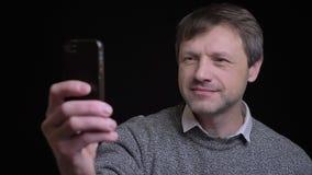 Всход крупного плана взрослого привлекательного кавказского мужчины принимая selfies по телефону и усмехаясь перед камерой сток-видео