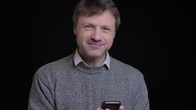 Всход крупного плана взрослой привлекательной кавказской мужской отправки SMS по телефону и усмехаться пока смотрящ камеру сток-видео