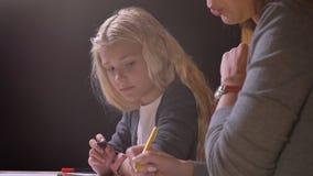 Всход крупного плана матери давая ее небольшой милой девушке урок и помогая ей с домашней работой с изолированной предпосылкой сток-видео