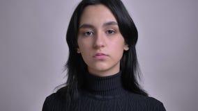 Всход крупного плана молодой привлекательной кавказской женской модели представляя перед камерой акции видеоматериалы