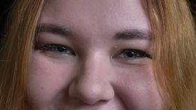 Всход крупного плана молодой полной женской стороны с серыми глазами смотря прямо на камере с усмехаясь жизнерадостным уходом за  видеоматериал