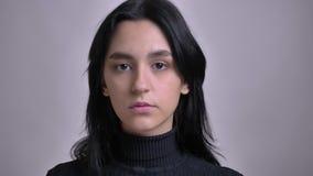 Всход крупного плана молодой сногсшибательной кавказской женской модели представляя в переднем od камеру с изолированной предпосы акции видеоматериалы