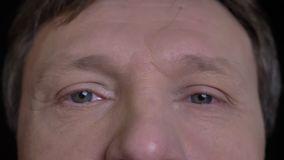 Всход крупного плана середины постарел кавказская мужская сторона с серыми глазами смотря прямо на камере видеоматериал